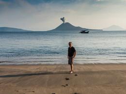 Tobias Schorr am Strand von Rakata. Im Hintergrund bricht der Anak Krakatau aus (c) Tobias Schorr