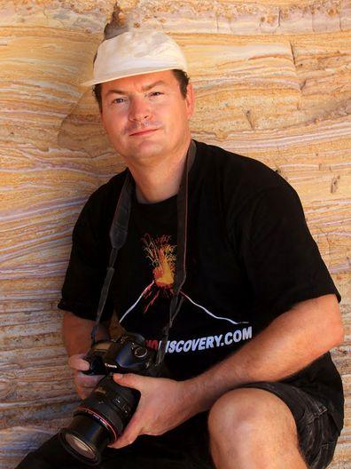 Tobias Schorr vor einer Wand mit vulkanischen Ascheschichten der Vulkaninsel Milos.
